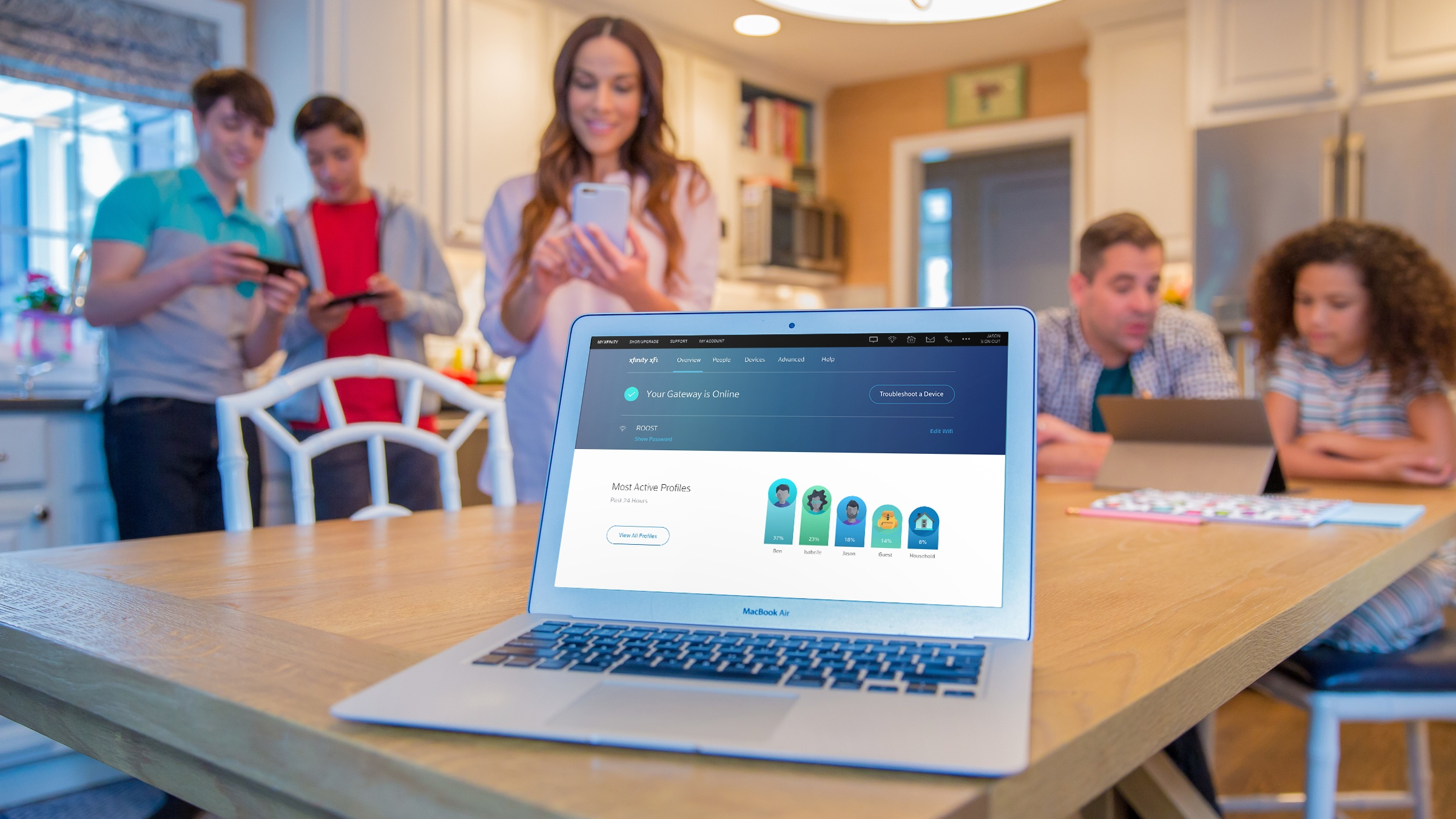 A family is gathered around a laptop displaying the status of their Xfinity xFi devices.