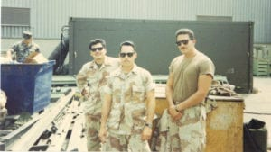 Mario Sanchez and two other members of the Marine Corps pose in front of military equipment.