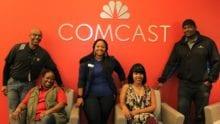 Members of Comcast's Black Employee Network stand in front of a Comcast logo.