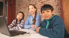 Three children sit at a table and use a laptop.