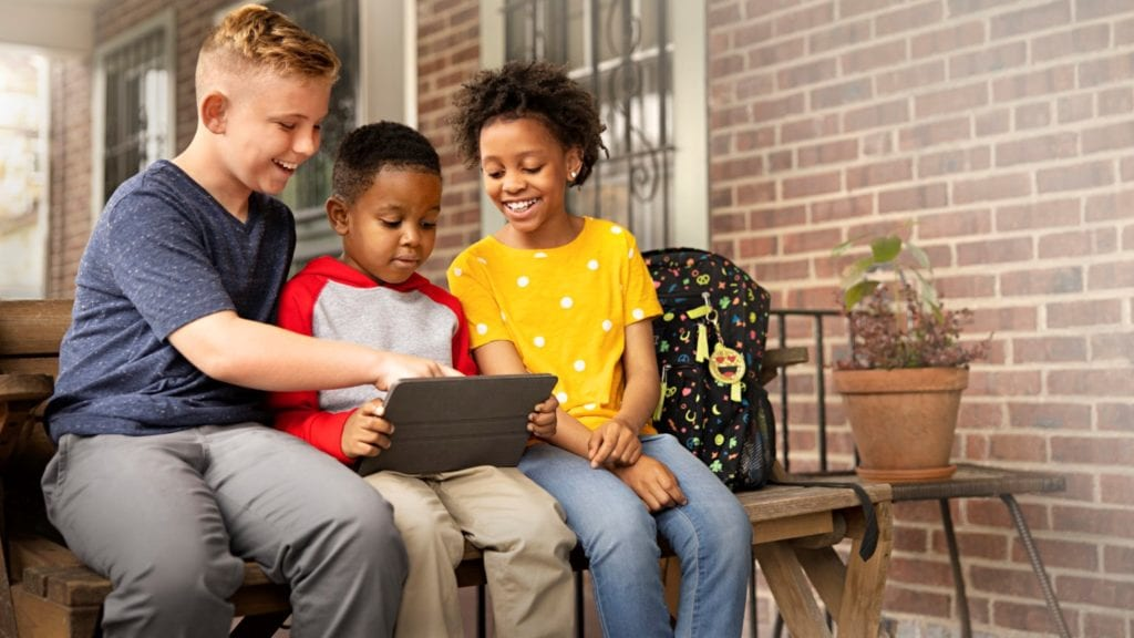 Three young students use a tablet to watch videos