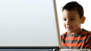 A young child uses a laptop to do homework
