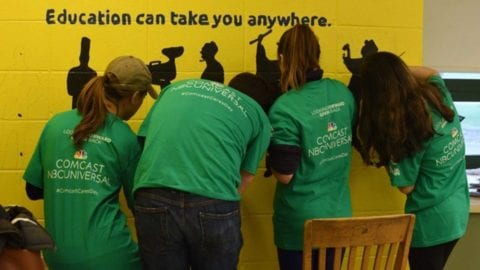 Comcast Cares Day volunteers painting mural