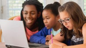 Three students gather around a laptop to study together