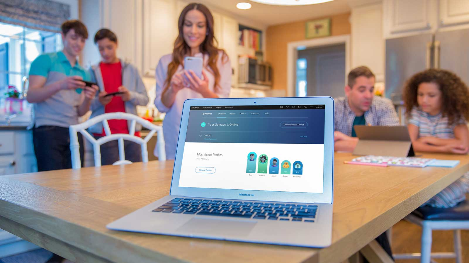 Family in kitchen using wireless devices
