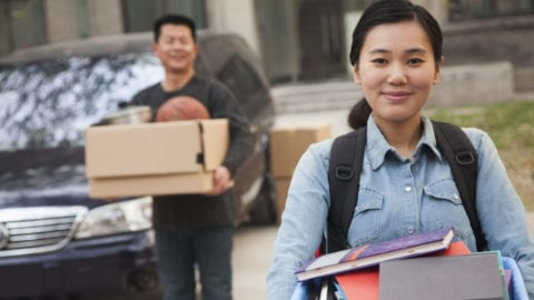 A student carries a box of books.