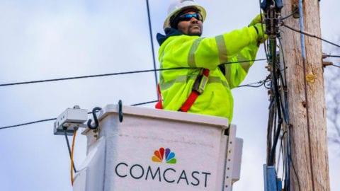 A Comcast technician services a telephone pole.