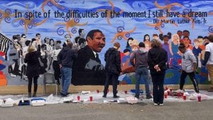 Community members painting a mural of Dr. Martin Luther King, Jr.