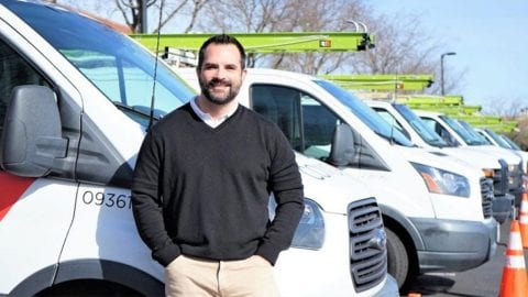Employee Mike Burnett standing in front of a Comcast truck