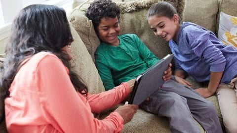 A family gathers around a tablet on a couch