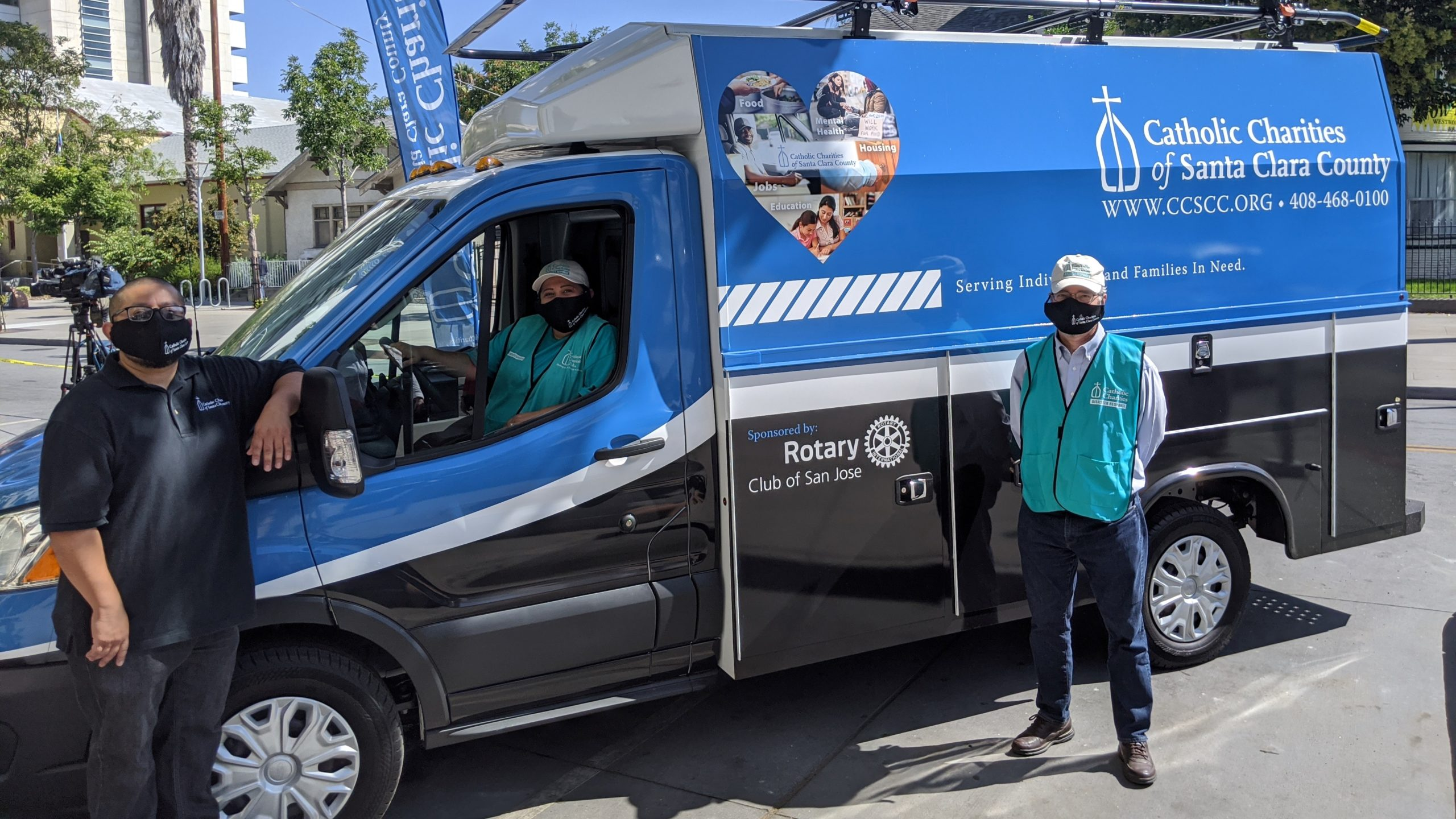 Volunteers in front of a Catholic Charities of Santa Clara County van