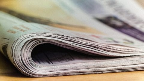 A folded newspaper on a desk.