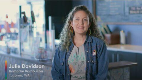 Julia Davidson smiles at the camera with long curly, brown hair, wearing a jean jacket and gray shirt.