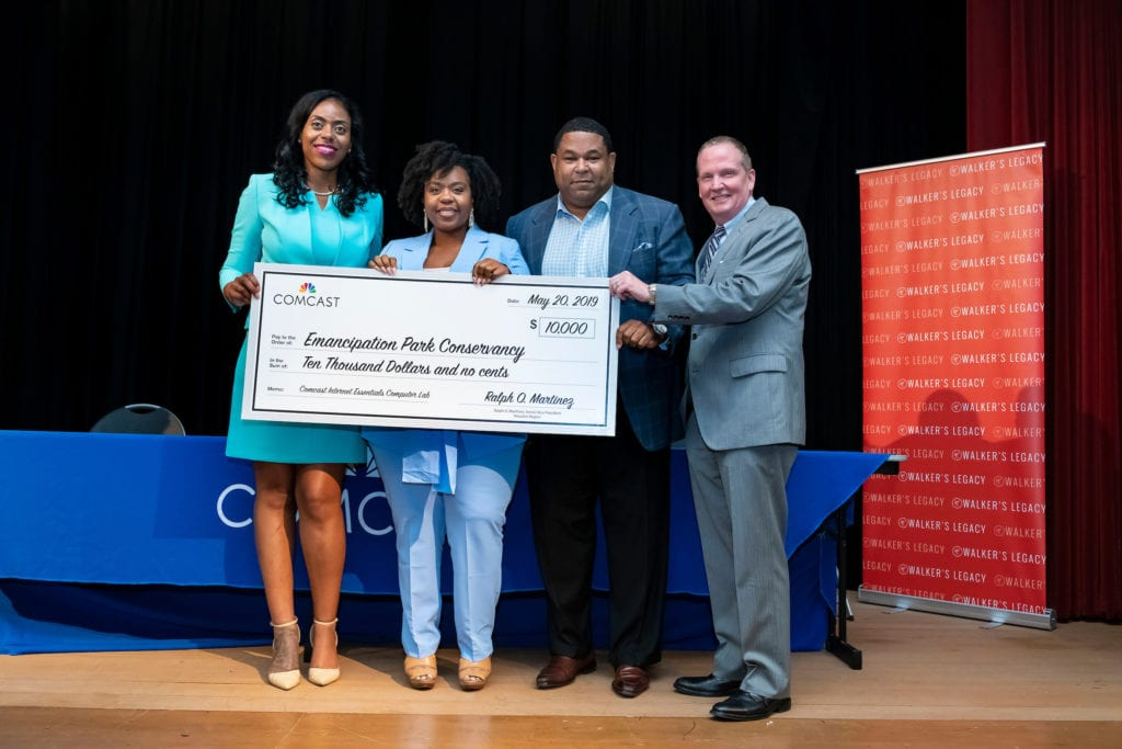 Four people onstage at the Women of Color in Tech event hold an oversized check made out to the Emancipation Park Conservancy