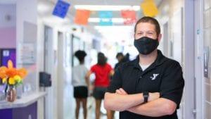 A masked YMCA instructor in a hallway