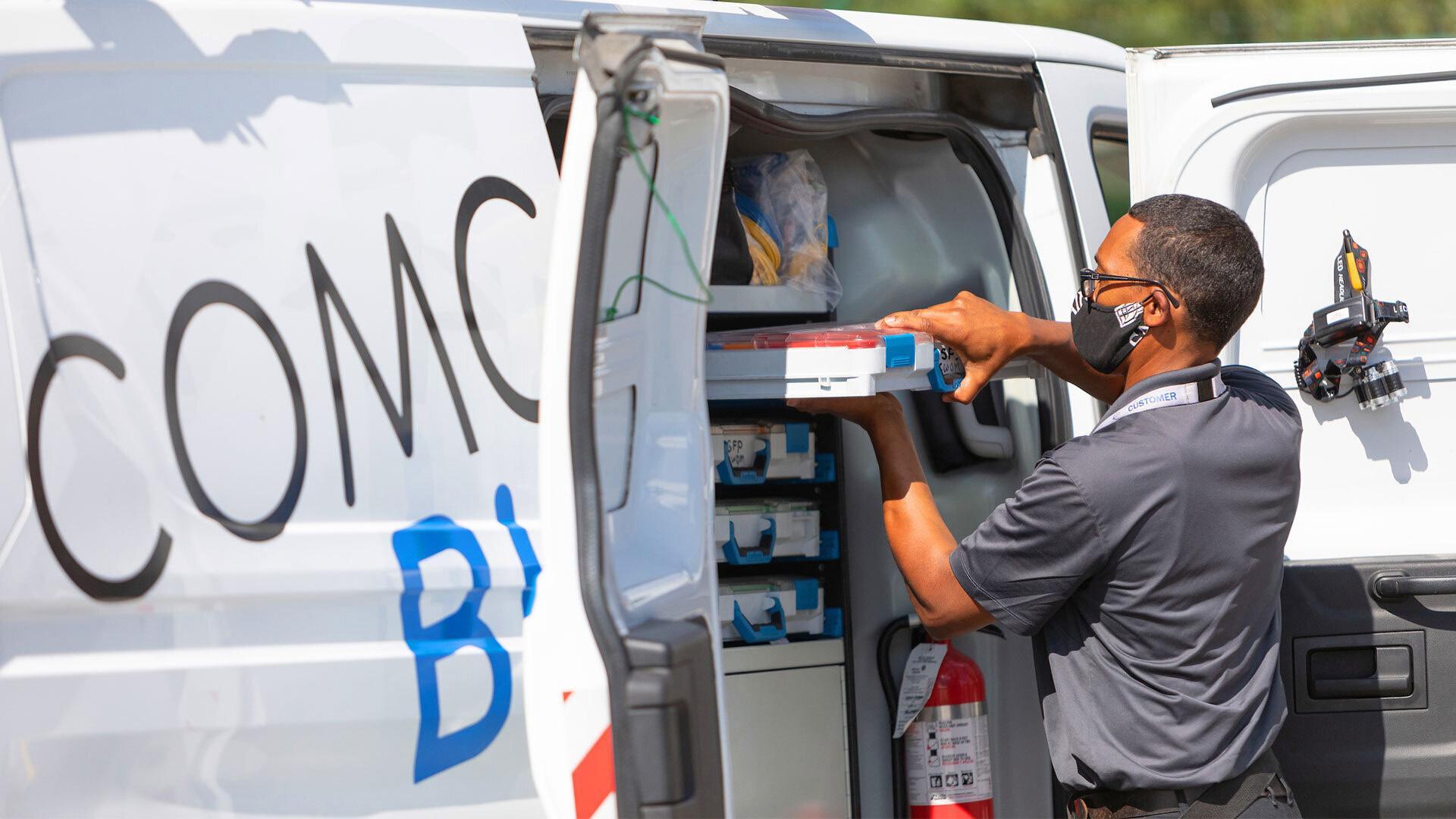 A Comcast technician unloads supplies from a van