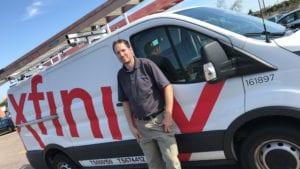 An Xfinity technician stands next to an Xfinity van.