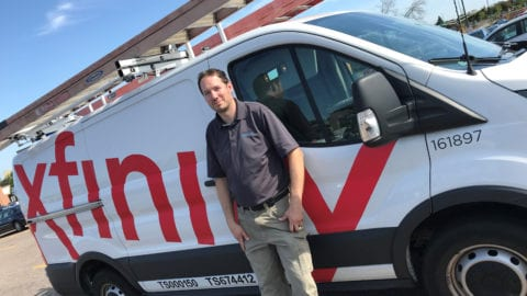 An Xfinity technician stands next to an Xfinity van.