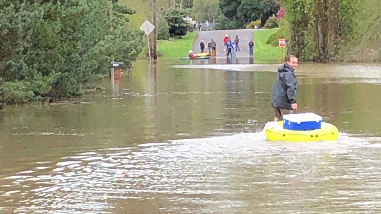 Eder Perez pulls an innertube full of groceries across a flooded road.