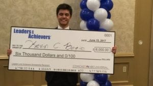 Kevin Begic holds and oversized check presented to him by the Leaders and Achievers Program.
