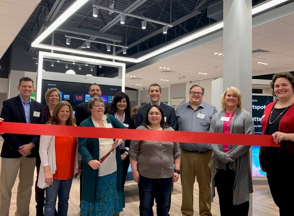 Employees of the XFINITY retail store in Muskegon cut a ribbon at the store's opening.