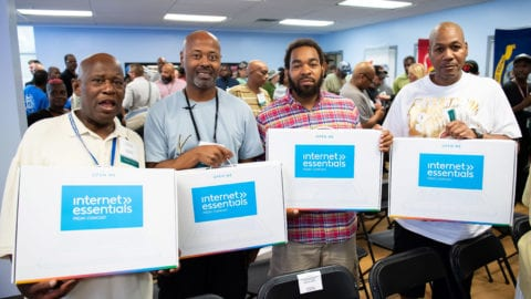 Four veterans hold up their Internet Essentials laptops at an event in Detroit.