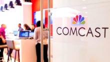 The Comcast logo on a glass door.