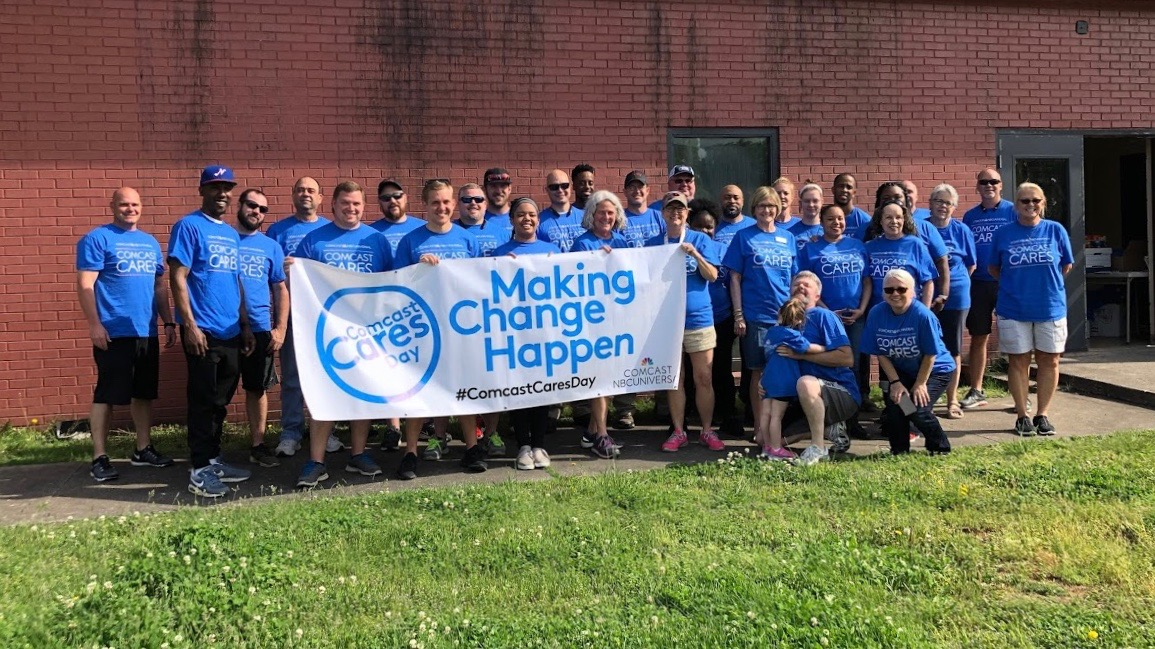 A large group of Comcast Cares Day volunteers hold a Making Change Happen banner.
