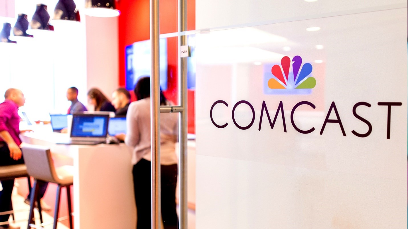 The Comcast logo on a glass door that opens into an employee workspace.