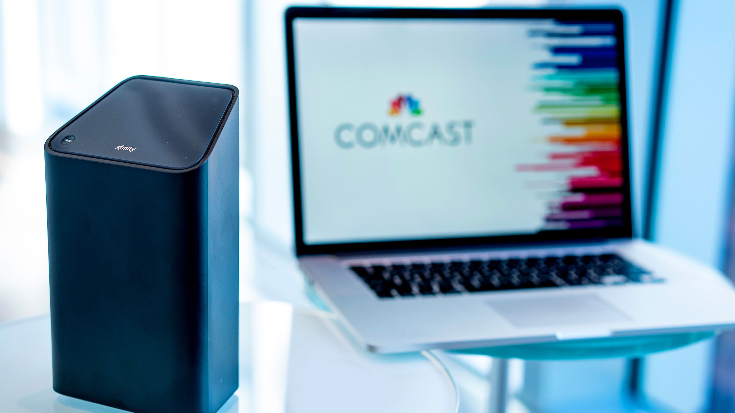 An Xfinity xFi Advanced Gateway and a laptop displaying the Comcast logo