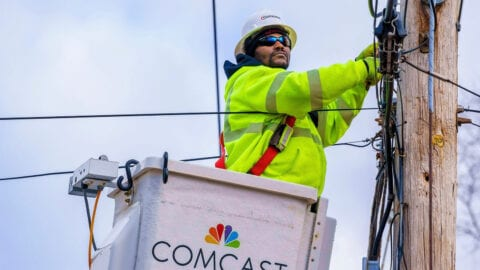 A Comcast technician repairs equipment on a telephone pole.