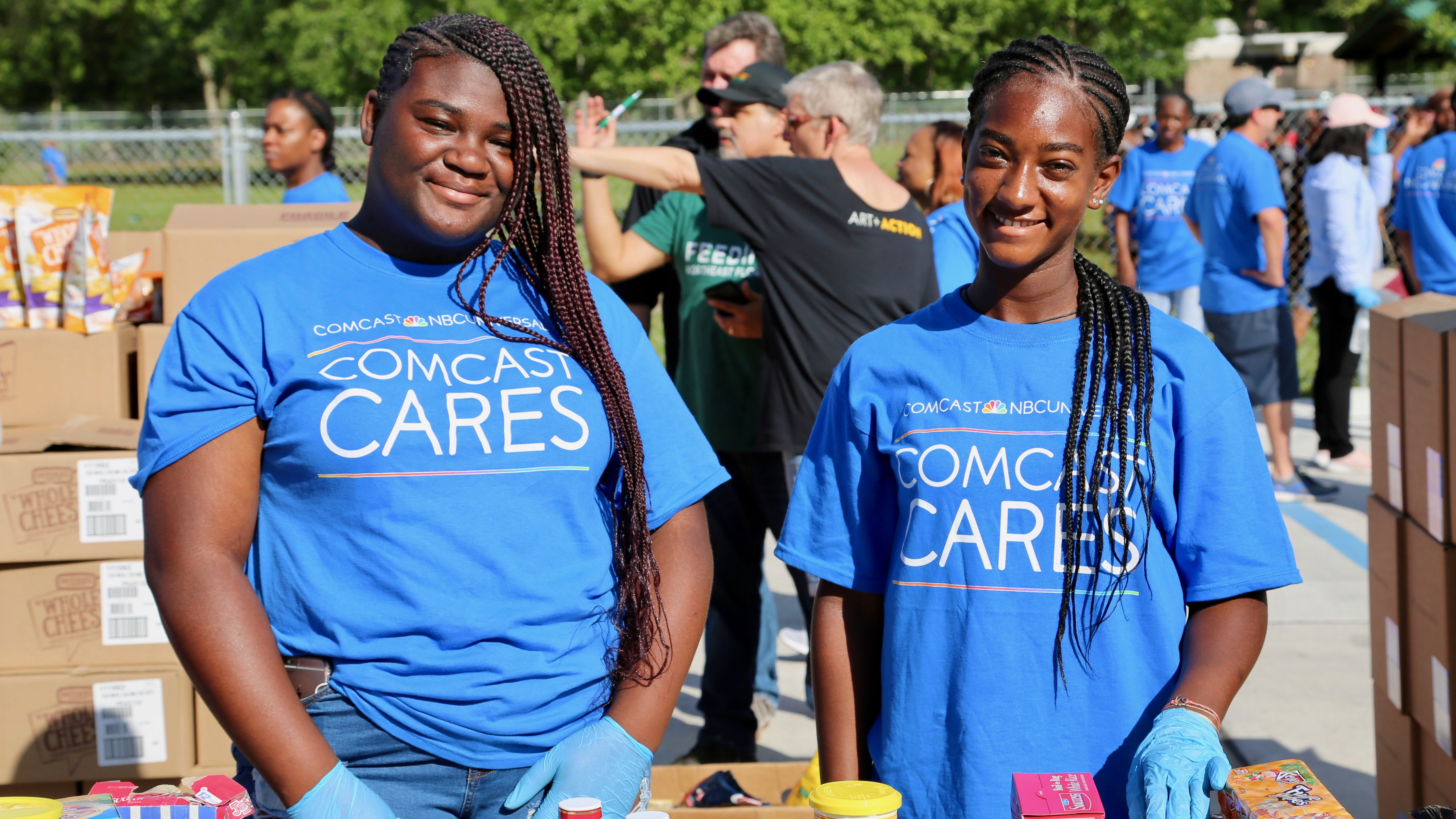 Comcast Cares Day volunteers prepare boxes of food for people in need.