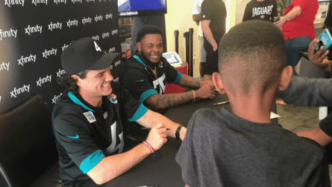 Members of the Jacksonville Jaguars sign autographs at an Xfinity event.