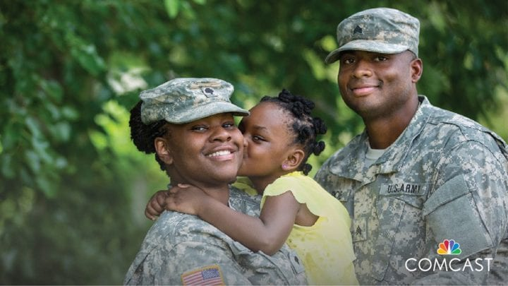 A male and female dressed in a military uniform holding a young child.