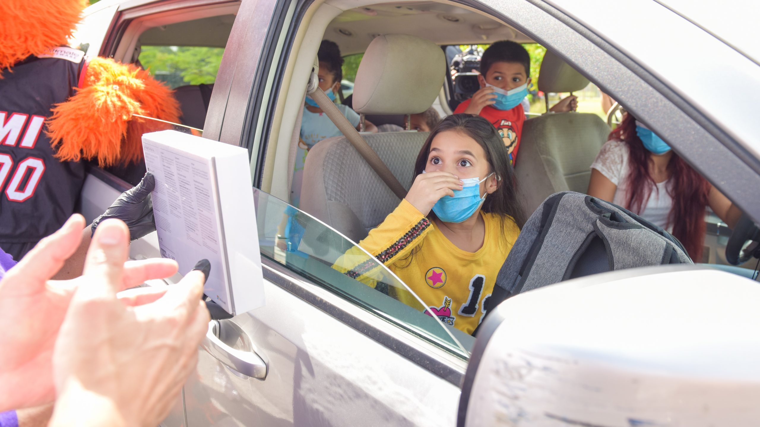 Children in a car exclaim with excitement