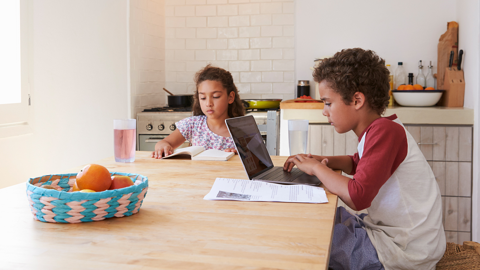 Two students do their homework at a kitchen table