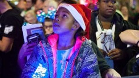 little girl wearing a Santa hat looking up