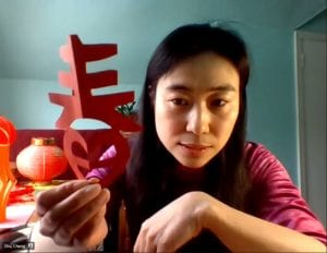 "Woman holding cut paper Chinese symbol for ""Spring"""