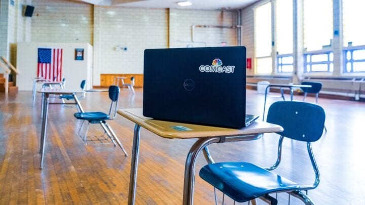 laptop with Comcast logo sitting on student desk in classroom