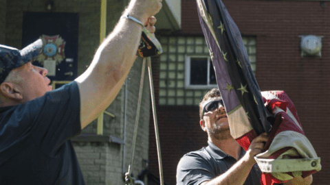 Comcast employees lowering American flag