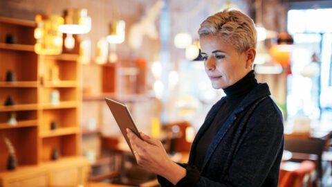 Woman looking at tablet computer inside her business