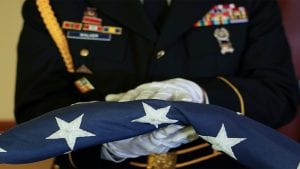 A member of the armed forces holds an American flag.