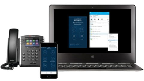A desk phone, mobile phone, and laptop display the Comcast Business app.