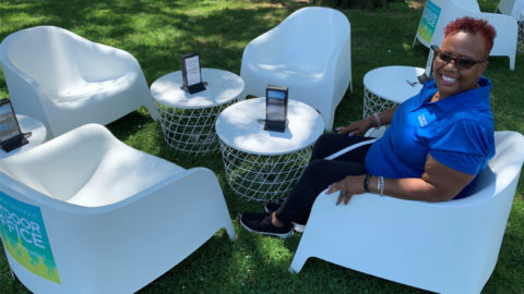 A Comcast Business technician sits in a chair on a lawn.