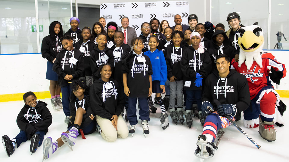 Rico Roman and Internet Essentials participants on the ice at an event in Washington D.C.
