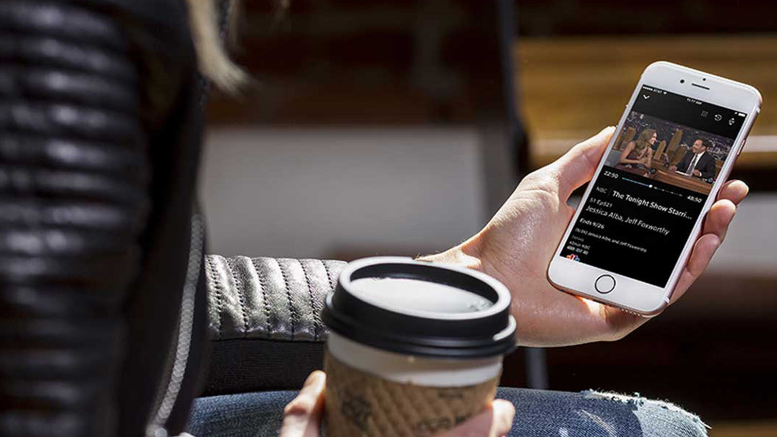 A person uses their mobile phone in a coffee shop.