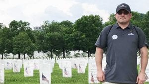 Michael Hackworth stands in a graveyard.