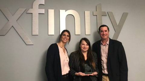 three people posing in front of an xfinity sign