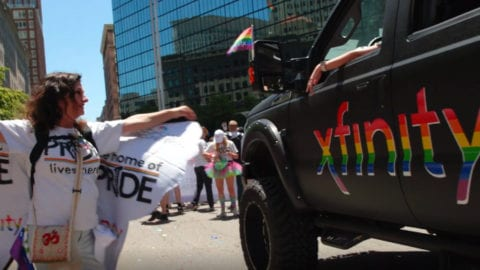 Participants in a Pride parade walk down a street.