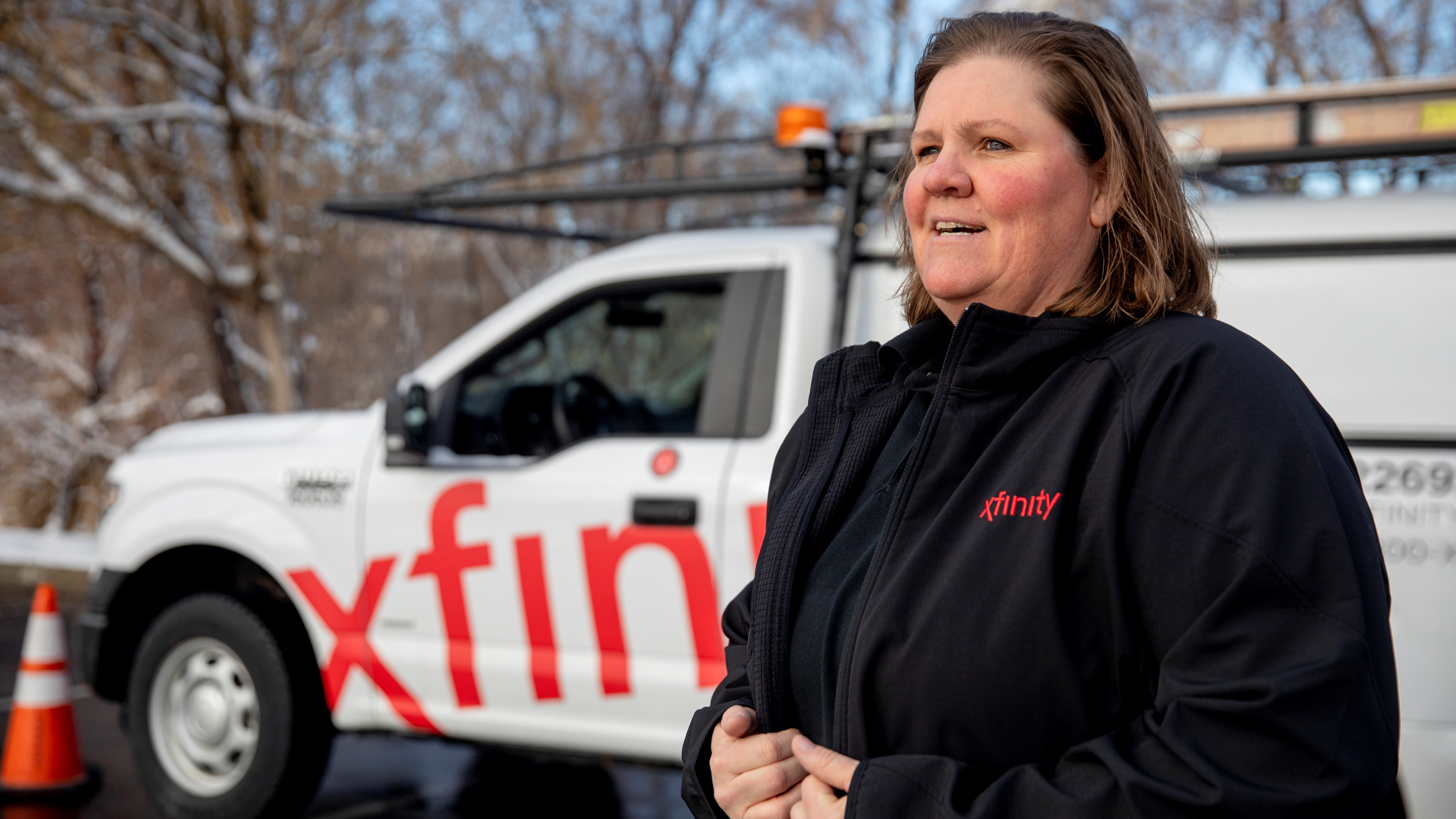 Michelle Hathenbruck stands in front of her Xfinity service van.